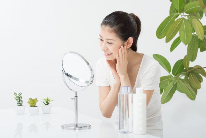 鏡を見ながら笑う女性の画像