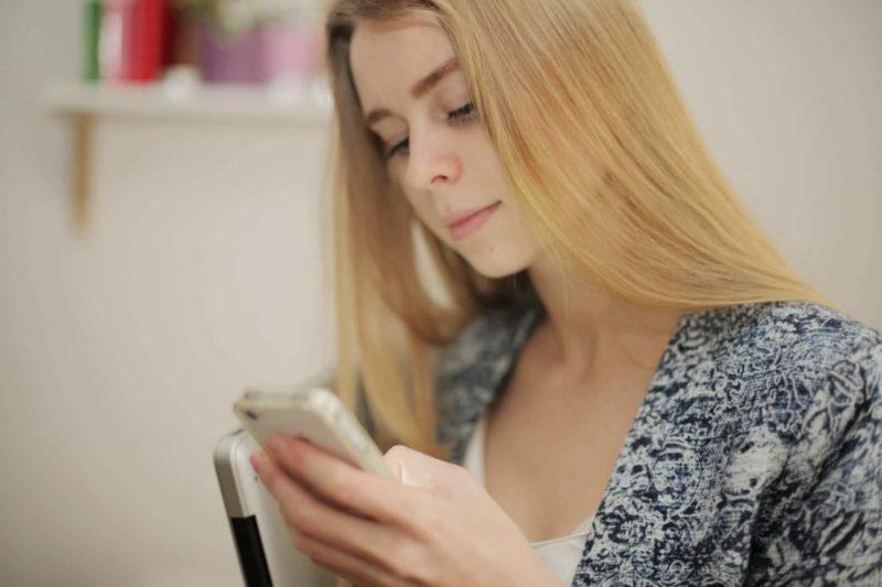 スマートフォンを持っている金髪で長髪の外国人女性
