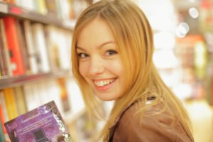 本屋で本を持っている外国人女性