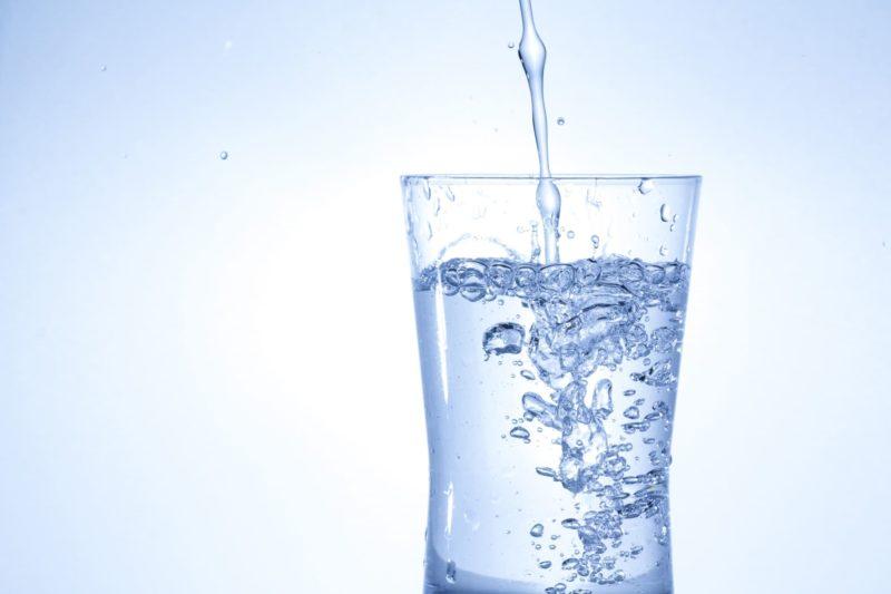 コップに水を入れている画像