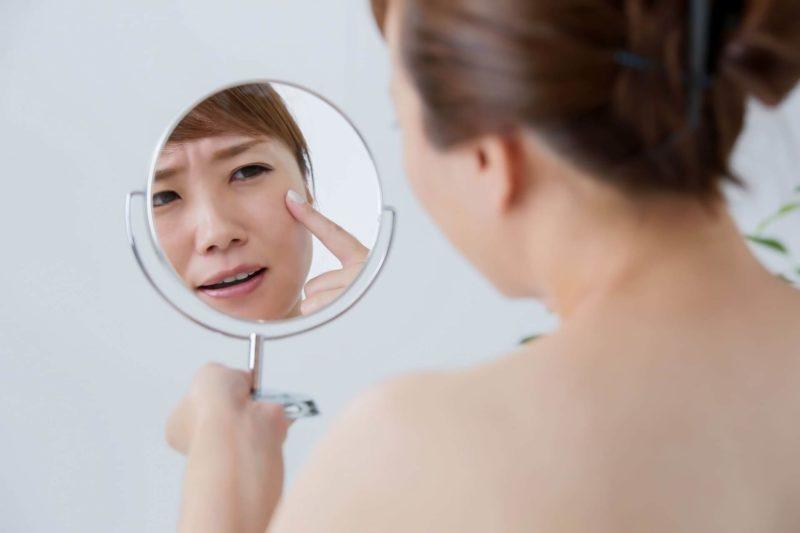 鏡で目元を気にする女性
