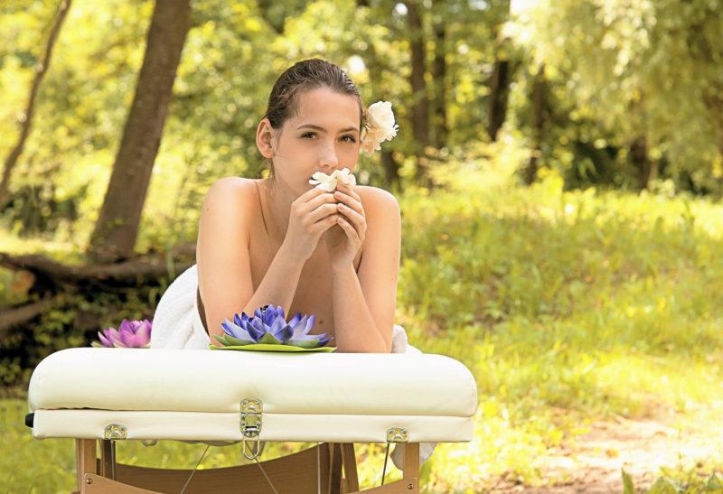 森の中でエステを受けて花の匂いを嗅いでいる女性