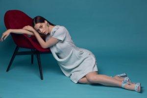 椅子にもたれかかり床に座っている外国人女性