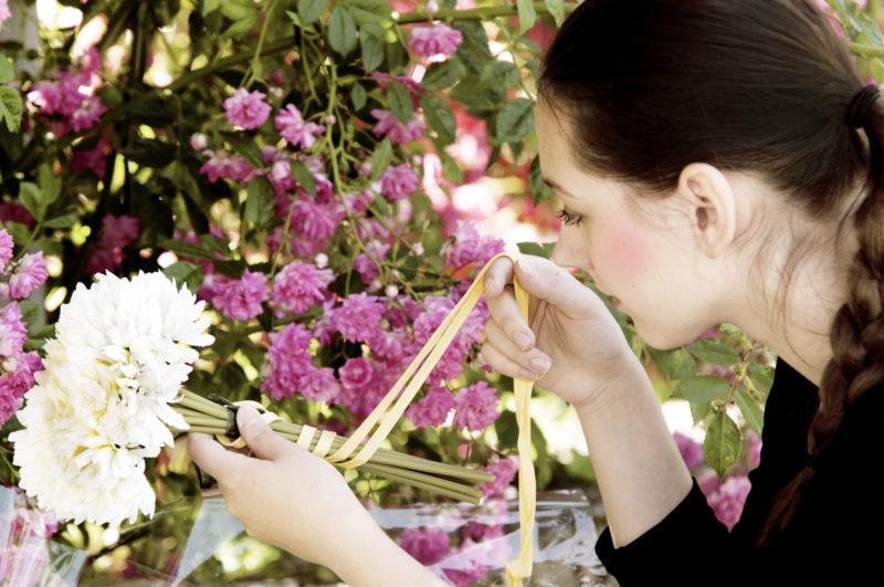 白い花を束にしている外国人女性
