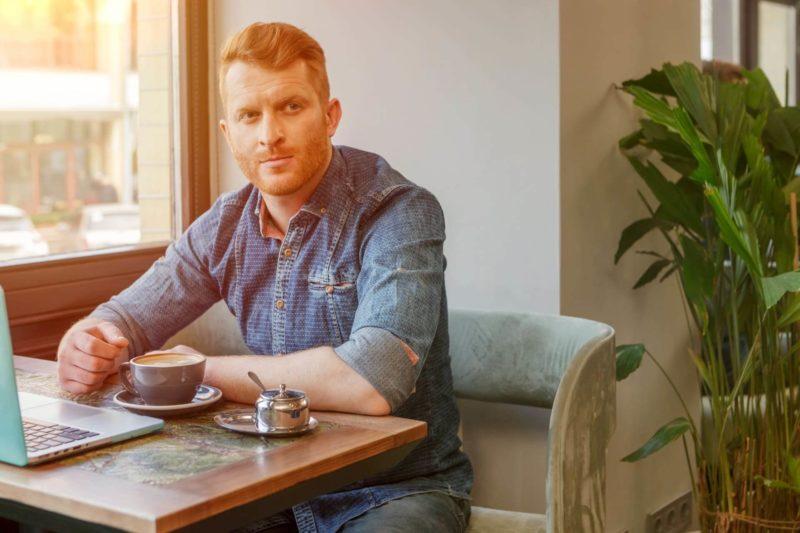 テーブルに座っているバリスタの外国人男性