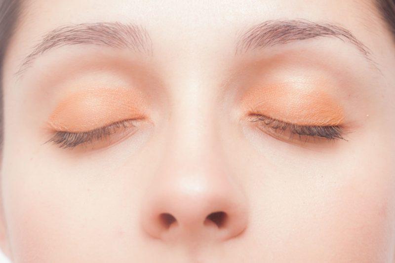 オレンジのアイシャドーを塗っている女性の顔のアップ
