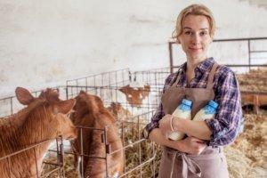 牛舎で牛乳瓶を抱えている外国人女性