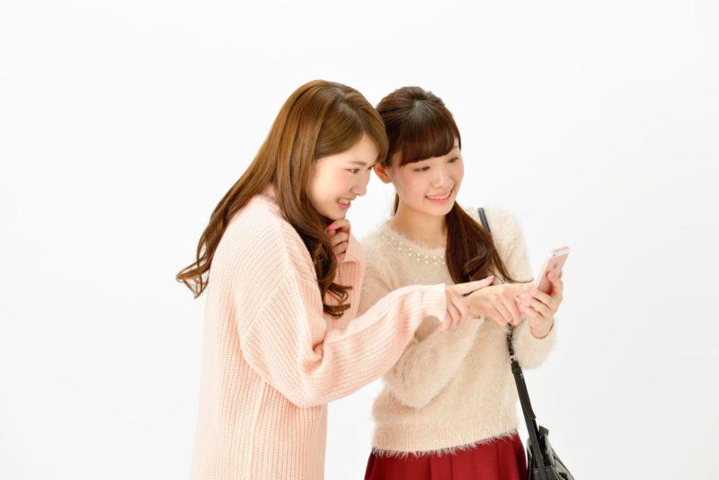 日本人の女の子2人がスマホを見て共感しあっている写真