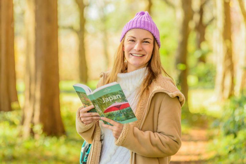 森の中でガイドブック片手に喜んでいる女性
