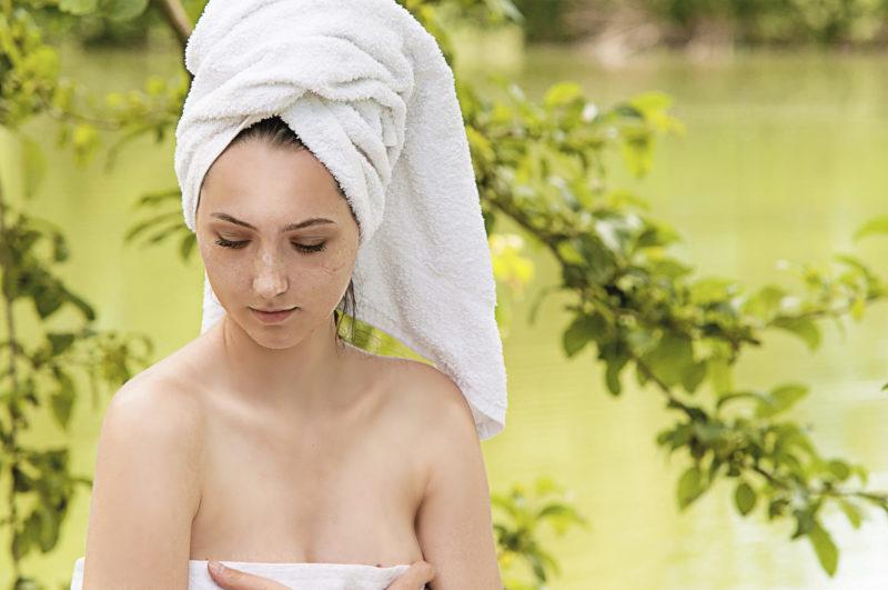 森と湖の中で体にタオルを巻いている女性