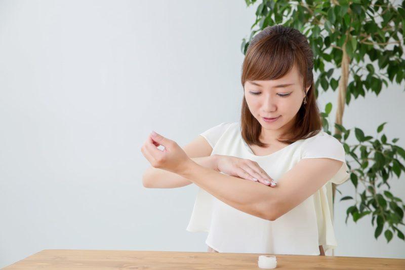 腕に保湿クリームを付けている女性
