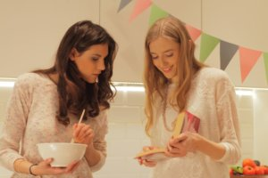 女の子二人が料理しながら何やら話している写真
