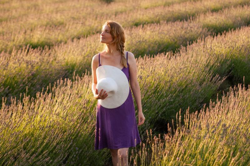 ラベンダー畑にいる紫の服を着用した帽子を持っている外国人女性