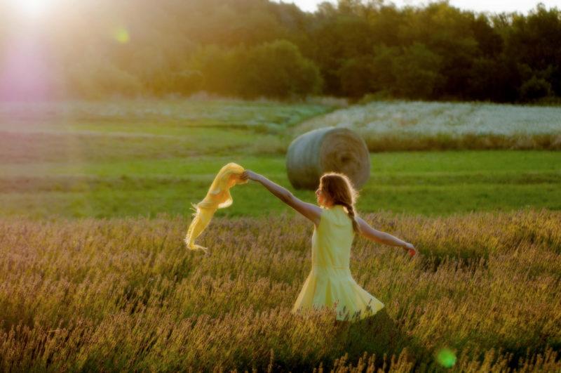 ラベンダー畑にいる黄色の服を着用したストールを持っている外国人女性