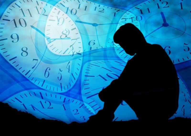 歪んだ時計と不安そうにしている人のイラスト