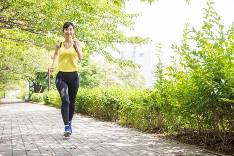 歩道をランニングする黄色と黒のウェアの女性