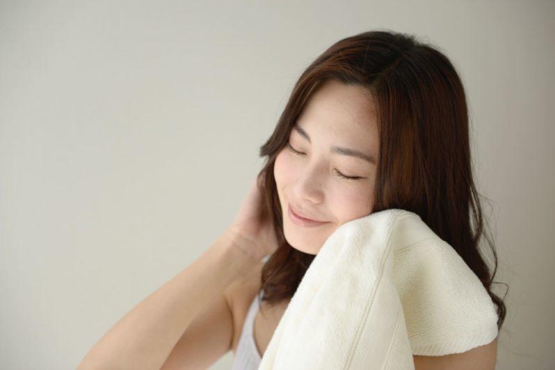 柔らかそうなタオルで顔を拭く女性