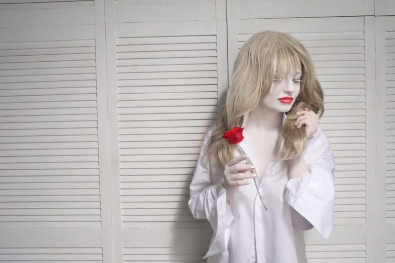 赤い花を持っている白い肌の女性の画像