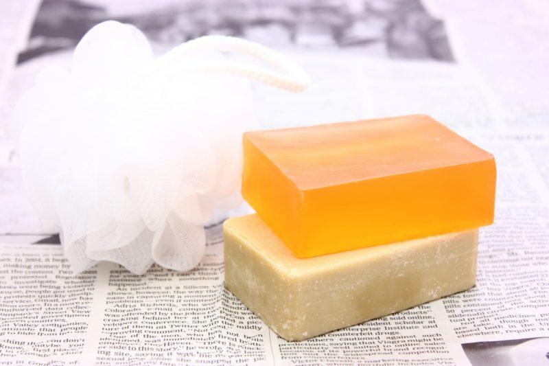 英字新聞の上の石鹸2つと洗顔ネット