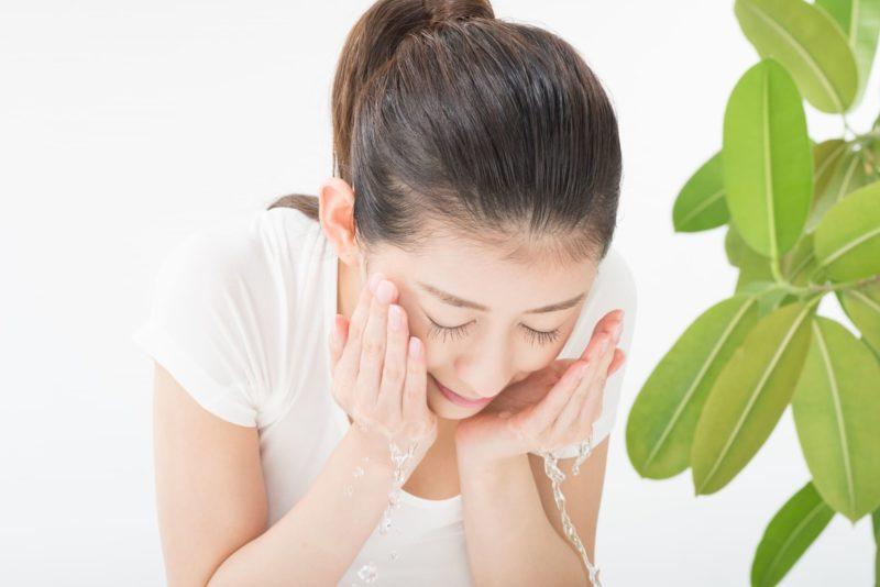 顔を洗う女性と観葉植物