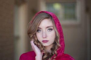 髪の毛に手を触れている赤ずきんの外国人女性