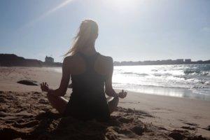 砂浜でヨガをしている外国人女性
