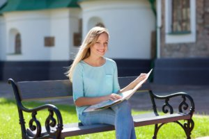 晴れたベンチに座って地図を見ている女性