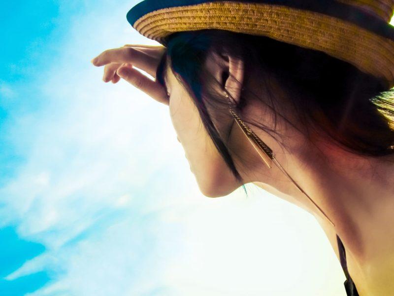 空を見上げている麦わら帽子を被っている女性