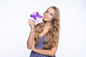 紫のプレゼントを持っている長い髪の女性