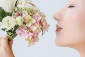 花のブーケを顔に近づけている女性