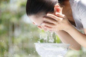 緑の背景で顔をパシャパシャ洗っている日本人女性