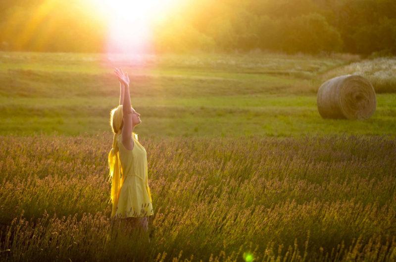 ラベンダー畑で日の光を浴びている黄色い女性