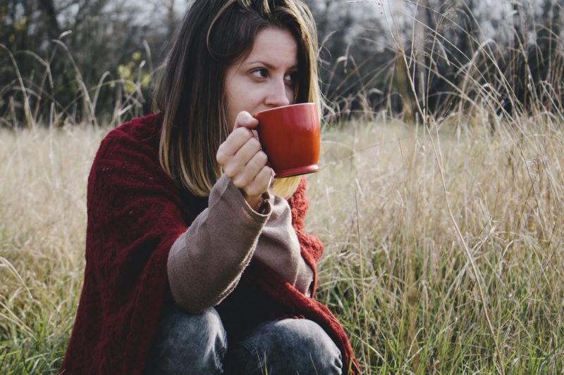 草原でお茶を飲んでいる女性