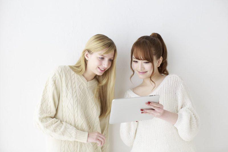外国人の友人とタブレットで調べ物をしている2人