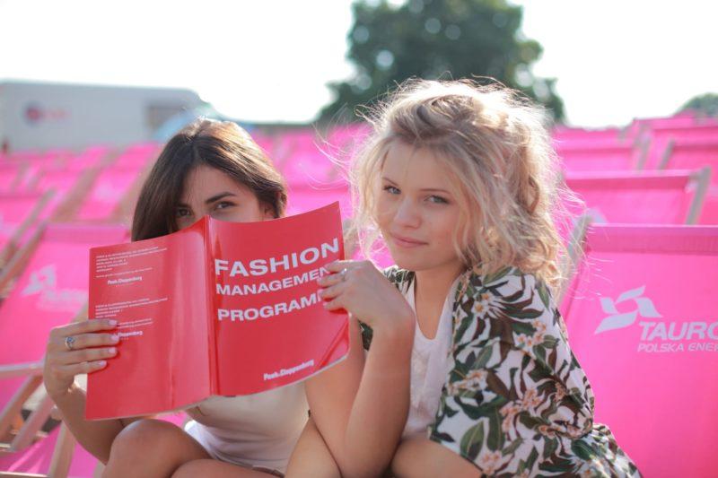 屋外のピンクシートでファッション誌を読んでいる女性二人