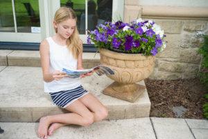 家の庭で一生懸命雑誌を読んでいる白い服の女の子