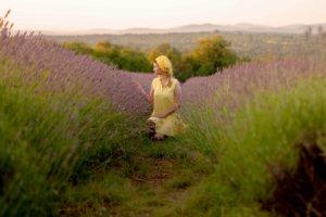 ラベンダーの花を見て触っている黄色い服の女性
