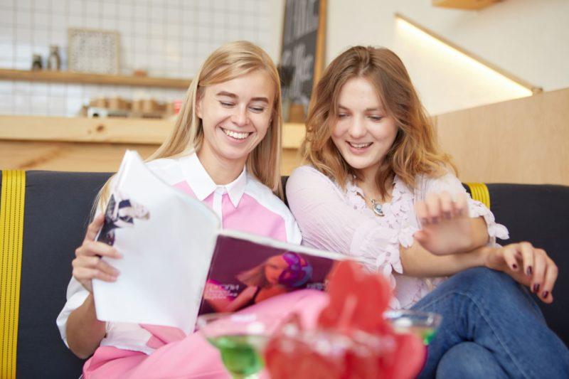 友達と二人でファッション雑誌を見て楽しんでいる外国人