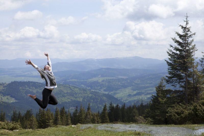 山の上で元気そうに跳ねる女性