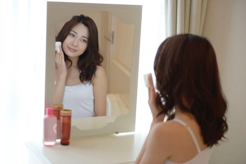 化粧台に向かって化粧をしている女性