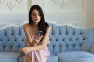 ソファーに座ってスマートフォンを操作している外国人女性