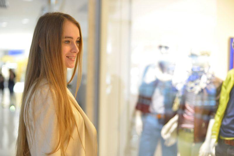 洋服のショーウインドーを眺めている女性