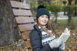 木製のイスで読書している冬装備の女性