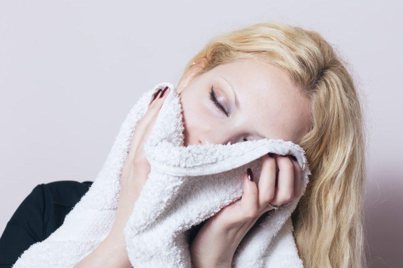 気持ちよさそうにタオルで顔を覆っている女性