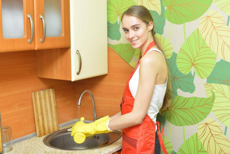 ゴム手袋をして、キッチンの水仕事をしている女性
