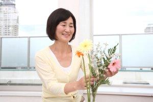 花を活けているシニア女性
