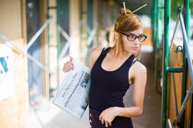 屋外で新聞を持って立っている外国人女性
