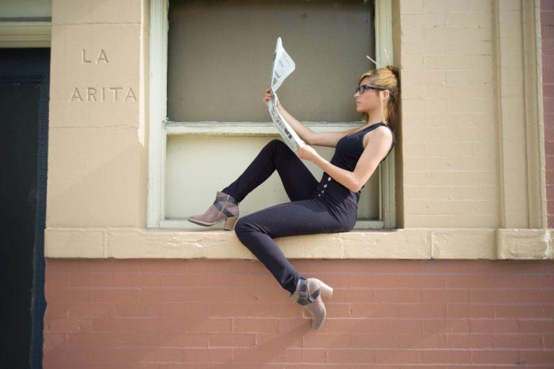屋外の壁に座って新聞を読んでいる外国人女性