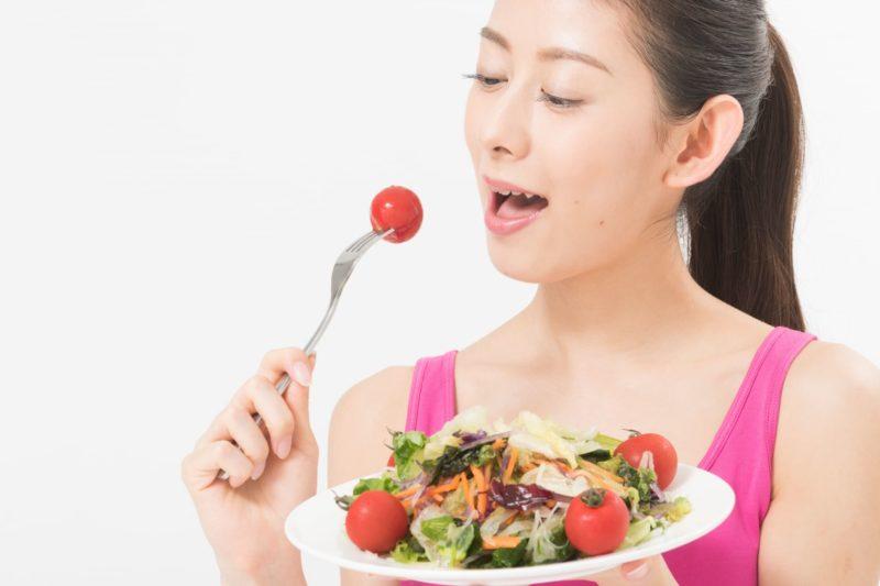 トマトの野菜サラダを食べてる女性