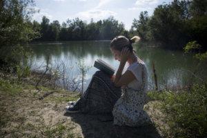 水辺のそばで座って本を読んでいる外国人女性